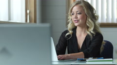 Young female customer service representative at work - stock footage
