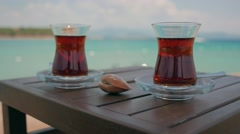 Two glasses of turkish tea on the table with Mediterranean Sea on the background Stock Footage
