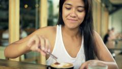 Young woman adding sugar into coffee and mixing sitting in cafe Stock Footage