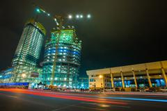 Construction at night with colorful blurred carlights against the dark sky - stock photo