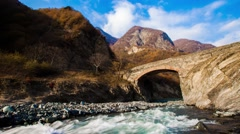 Mountain bridge over the river in Qakh, Azerbaijan. Time lapse fast flowing rive Stock Footage