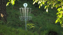 Disc golf basket number one with chains swaying slowly at a disc golf course Stock Footage