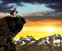 Cyclist on bike at sunset in Pennine Alps Stock Photos