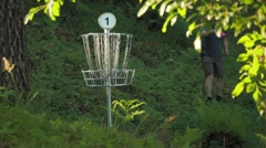 Male disc golf player throws a putter in the basket and picks up the disc Stock Footage