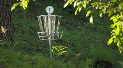 Two disc golf putts are thrown into the basket with jingling metal chains Stock Footage