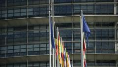 Zoom out of European Union country flags with European Parliament building in Stock Footage