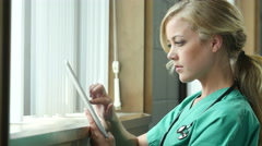 Young nurse using an ipad/tablet in a medical setting, close up Stock Footage