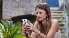 Stock Video Footage of teenager composing text messages on her smartphone: sending messages