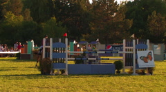 HORSE AND FEMALE RIDER JUMPING OVER OBSTACLES IN HORSE SHOW AT DUSK Stock Footage