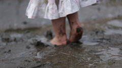 SMALL CHILD PLAYING AND JUMPING IN MUD Stock Footage