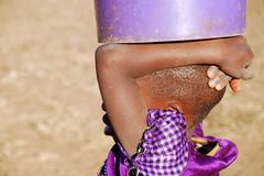 An African child with a bucket of water - Pomerini - Tanzania - Stock Photos