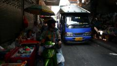 Small songthaew truck slowly pushing through narrow street, squeezed way Stock Footage