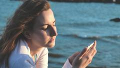 Woman in love writing and reading messages with the smartphone by the sea Stock Footage