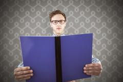 Stock Photo of Composite image of geeky student reading a book