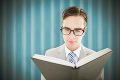 Stock Photo of Composite image of geeky preacher reading from black bible
