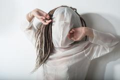Beautiful girl with dreadlocks poses in white suit - stock photo