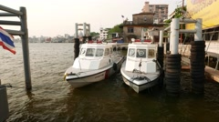 Two white police boats standing at pier, wave on water, front view Stock Footage