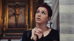 Young woman praying inside a catholic church: God, Christ, religion, christian Arkistovideo