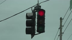 Red Stop Light Swinging In The Wind On Cloudy Day Stock Footage
