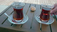 Two glasses of turkish tea on the table with wooden table on the background in Stock Footage