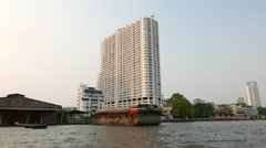 Supalai River Place condominium skyscraper on Chao Phraya bank, seen from boat Stock Footage