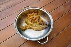 Pound eggplant in pot on wood table Stock Photos