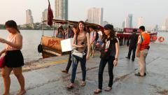Cheerful happy people debark from express boat, evening time, Chaophraya pier Stock Footage