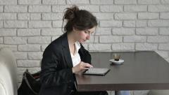 Worried and uncertain businesswoman checking her work on tablet computer in cafe Stock Footage
