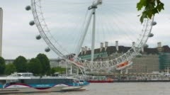 Establishing shot of tourist boat on River Thames and London Eye Wheel - stock footage