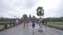 post sunrise - tourists walk away from Angkor wat in rain - stock footage