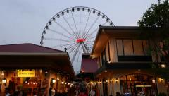 Big observation wheel in dusk, theme houses on foreground, shifting perspective Stock Footage