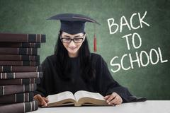 Beautiful girl with mortarboard reading books Stock Photos