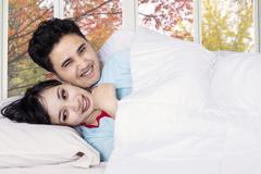 Couple joking and laughing on bedroom - stock photo
