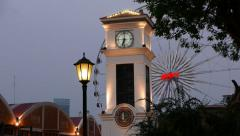 Clock tower against illuminated observation wheel in twilight, telephoto view Stock Footage