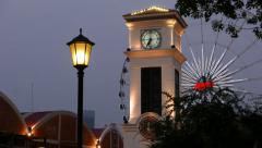 Lantern on pole, illuminated clocktower and observation wheel, perspective shift Stock Footage