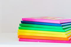 Multi colored books in stack on the light-coloured bookshelf Stock Photos