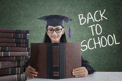 Girl with mortarboard and books back to school Stock Photos