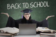 Stock Photo of Joyful learner with mortarboard back to school