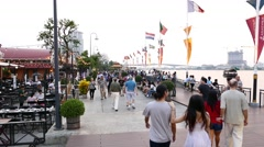 Lively river side promenade, people walking around, enjoying the evening time Stock Footage
