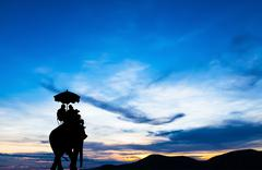 Stock Photo of silhouette elephant with tourist at sunset