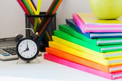 Black alarm clock and multi colored books in stack Stock Photos