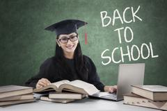 Student with mortarboard back to school and studying - stock photo