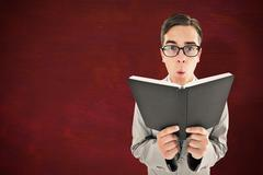 Composite image of geeky preacher reading from black bible - stock photo