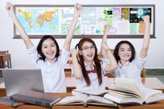 Three excited schoolgirls raise hands in the class - stock photo