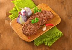 Beef Burger Patties on cutting board - stock photo