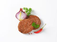 Two Grilled Beef Burger Patties - stock photo