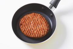 Pan-fried beef burger patty in pan - stock photo