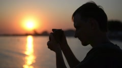 Photographer working at sunset on the beach - stock footage