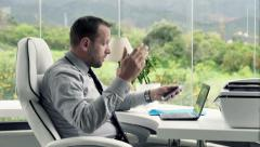 Shocked, overwhelmed businessman working with laptop and smartphone in office - stock footage