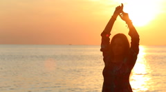 Silhouette of girl posing against sunrise above sea Stock Footage